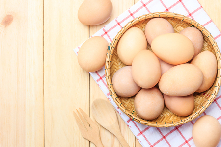 basket weaving: Fresh egg in the basket weaving over wooden table background, Top view with copy space and text. Stock Photo