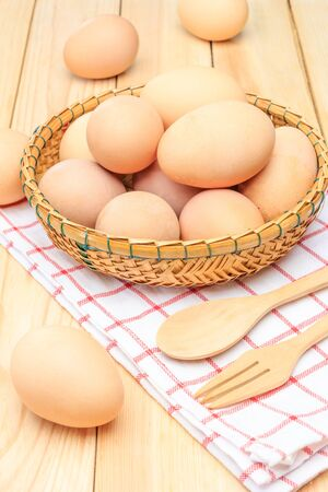 basket weaving: Fresh egg in the basket weaving over wooden table background, Closed up Stock Photo