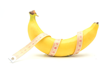 banana skin: Measuring tape wrapped around a banana isolated on a white background, Concept of diet.