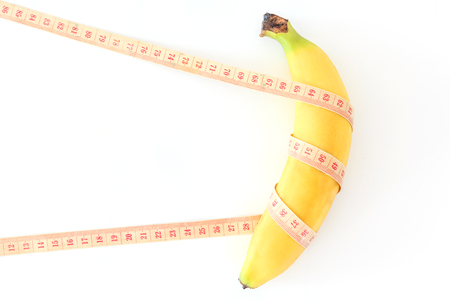 Measuring tape wrapped around a banana isolated on a white background, Concept of diet.