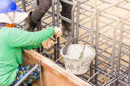 workers hands using steel wire and pincers to secure rebar before concrete is pour over it, Construction site worker