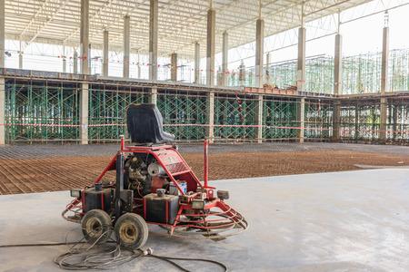 Double puissance truelle de finition plancher de béton au chantier de construction, surface de béton lisse. Banque d'images - 68439459
