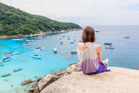 Young woman sitting on a cliff view tropical beautiful crystal clear sea at tropical island, Similan Islands National Park, Phang Nga, Thailand