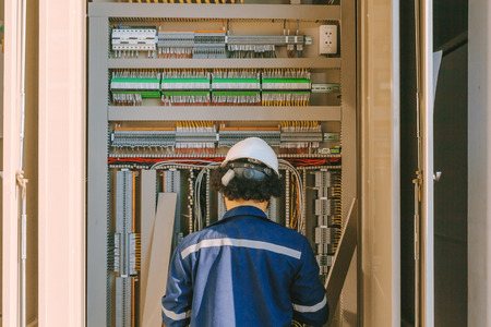 plc: Instrument technician on the job check wiring on PLC cabinet Stock Photo