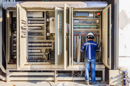 Instrument technician on the job check wiring on PLC cabinet Archivio Fotografico