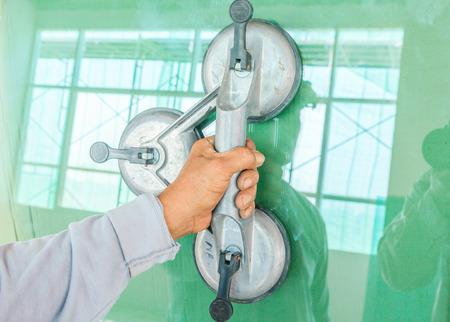 Mejoras para el hogar, la renovación - el trabajador de la construcción de azulejos es azulejos, adhesivo de piso de baldosas de cerámica Foto de archivo