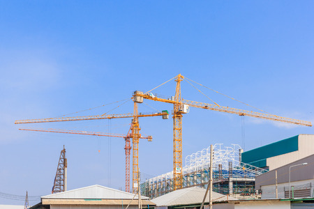 Industrial construction cranes and building in a beautiful blue sky background Stock Photo