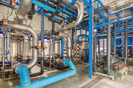 Large industrial water treatment and boiler room. Shiny steel metal pipes and blue pumps and valves. Zdjęcie Seryjne