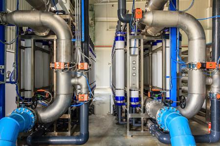 Duża przemysłowa oczyszczalnia wody i kotłownia. Błyszczące stalowe rury metalowe i niebieskie pompy i zawory.