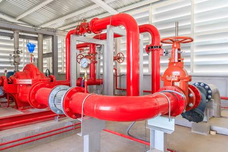 Stazione di pompaggio antincendio industriale per tubazioni di irrigazione a pioggia e sistema di allarme antincendio. Condotte, pompa dell'acqua, valvole, manometri. Archivio Fotografico - 75641284