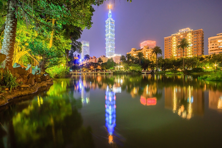 Lakeside scenery of Taipei 101 Tower among skyscrapers in Xinyi District Downtown at night with view of reflections on the pond in an urban park ~ Romantic nightscape of Taipei city Stock Photo