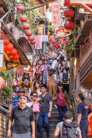 mining town: JIUFEN, TAIWAN - APRIL 30, 2017: Tourists walk down famed steps in Jiufen. A gold mining town developed under Japanese rule, the city now attracts visitors for its nostalgic scenery.