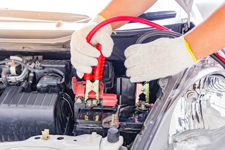 power cables: Charging car battery with electricity trough jumper cables,red and black Jumper cables Stock Photo