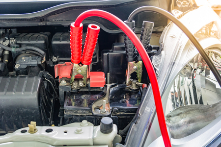 Charging car battery with electricity trough jumper cables,red and black Jumper cables 写真素材