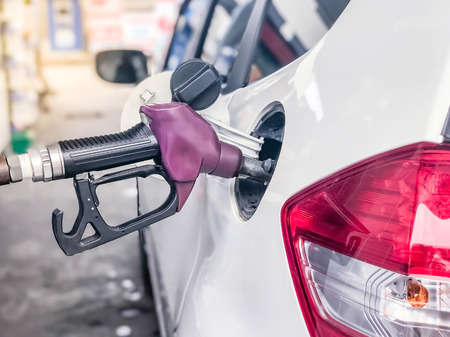 fuelling pump: Fuel nozzle to add fuel in car at petrol station.