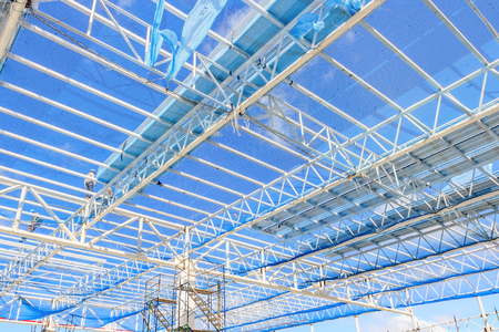 Structure of steel roof frame for building construction on blue sky background.