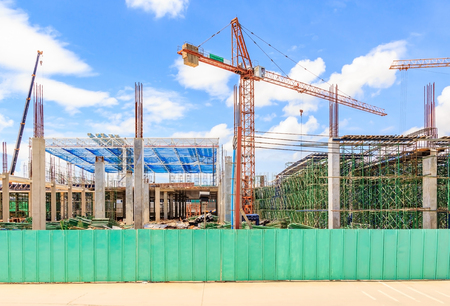 Construction site. Construction cranes and high-rise building under construction against blue sky Stock Photo
