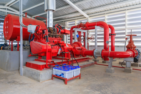 Industrial fire pump station for water sprinkler piping and fire alarm control system. Pipelines, water pump, valves, manometers. Reklamní fotografie - 80757088