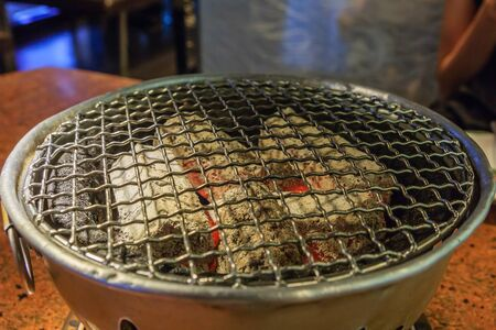 Empty hot barbecue grill with flames and copy space in korea style, Selective Focus Stock Photo