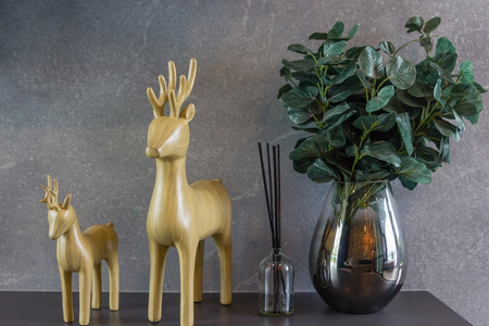 air diffuser: home interior decoration: Wood carving deer and vases with aromatic bamboo sticks, perfume diffuser and freshener in bathroom on brown wooden shelves