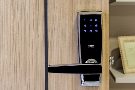 electronic door lock with card access on wooden door in apartment, safety area for high security