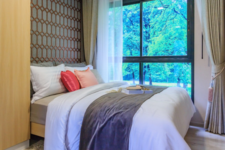 suite: set of pillows on bed in cozy bedroom interior design