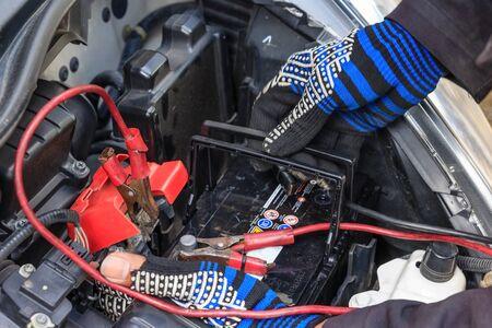 A car mechanic replaces a battery, selective focus