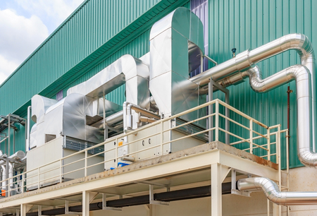 air-cooled chillers and piping system in new building factory rooftop with blue sky background Stockfoto