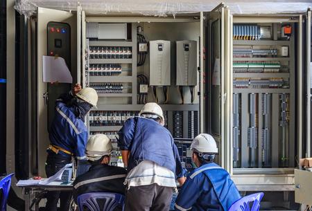 Ingenieur die aan controle en onderhoudsapparatuur werkt bij bedrading op PLC kabinet, ingenieur die status controleren opstaat omhoog transformator Stockfoto