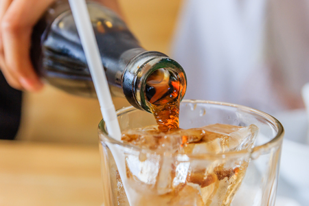 Close up of Pouring cola in a glass from a bottle