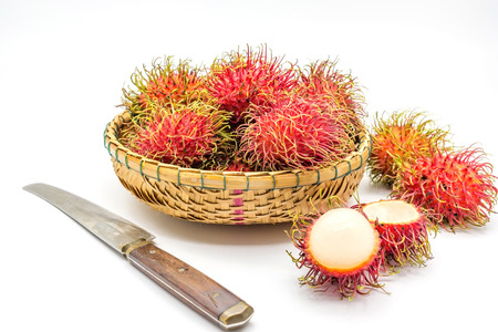 fresh tropical rambutan fruits over basket with knife on a white background, fruit in Thailand