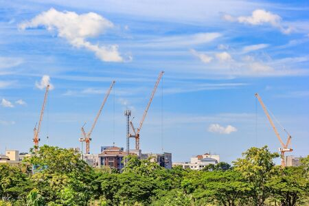 Construction site. Construction cranes and high-rise building under construction against blue sky.