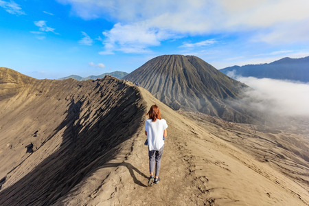 Female tourist walking through on the craters of Gunung Bromo and Sumeru volcanoes in Java, Indonesia Stock Photo