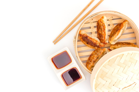 Japanese food, Gyoza dumplings in bamboo basket, serve with chopsticks isolated on a white background. Top view with copy space and text.