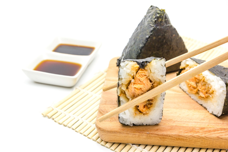 Japanese salmon rice wrapped in seaweed on wood plate isolated on white background with Copy space and text. Stock Photo