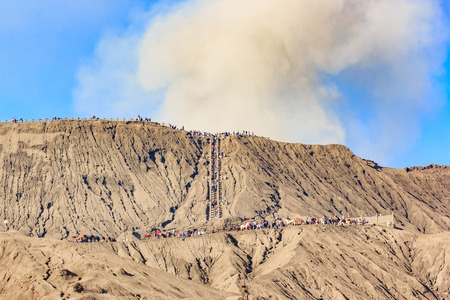 Many tourists walking to crater of Bromo volcano close-up with erupting smoke in Bromo Tengger Semeru National Park, East Java, Indonesia. Stock Photo