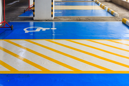 Handicap symbol on road, traffic and pedestrians on parking space Stock Photo