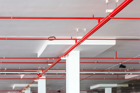 Fire sprinkler system with red pipes is placed to hanging from the ceiling inside of an unfinished new building. Standard-Bild