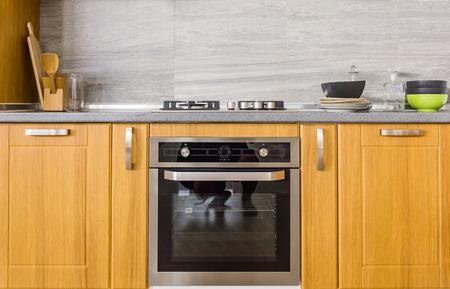 Keukenkasten met metalen handgrepen en ingebouwde elektrische oven Stockfoto