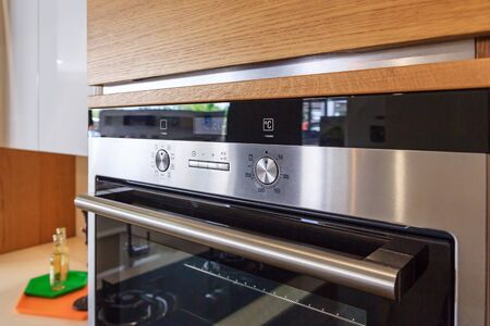 kitchen cabinets: Kitchen cabinets with metal handles and built-in electric oven