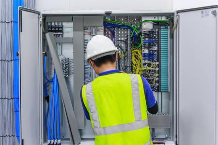 전기 스크루 드라이버 매크로 릴레이 및 터미널 블록 전기 캐비닛의 배경에 전선을 연결합니다.