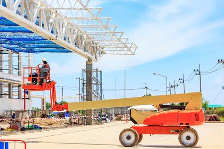 Lavoratore su una piattaforma di sollevamento idraulico Scissor Piattaforma verso un tetto di fabbrica in un cantiere Archivio Fotografico - 85086232
