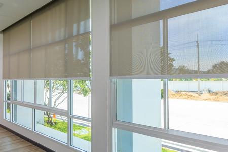 Rolljalousien an den Fenstern, die Sonne dringt nicht in das Haus ein. Fenster in den Innenrollläden. Schöne Jalousien auf dem Fenster, die Sonne und Hitzeschutz, die perfekte Fenster Innendekoration Standard-Bild