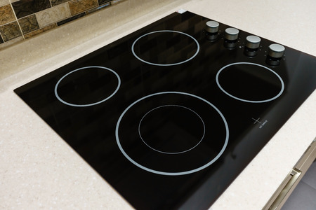Modern black induction stove, cooker, hob or built in cooktop with ceramic top in white kitchen interior Imagens - 85193361