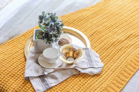 Gold tray of coffee cup with vase of plant on bed in luxury black bedroom at home