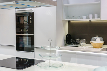 Modern kitchen furniture with contemporary kitchenware like hood, black induction stove, faucet and sink in house. Фото со стока