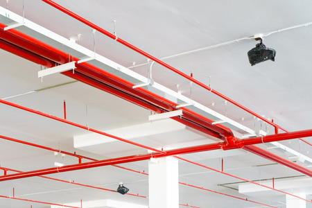 Fire sprinkler system with red pipes is placed to hanging from the ceiling inside of an unfinished new building. Stock Photo