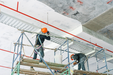 Travailleur installant un chemin de câbles avec un câblage électrique disposé au plafond de la plateforme offshore. Banque d'images - 85558272