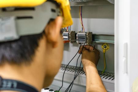 Elektricien met een macro van de schroevedraaier verbindt draden op de achtergrond van elektrokabinet met relais en eindblokken. Stockfoto