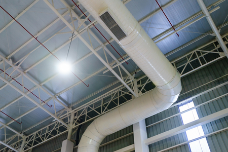 HVAC duct air conditioner ventilation pipes system in white insulation material hanging from the ceiling inside new building. Stock Photo